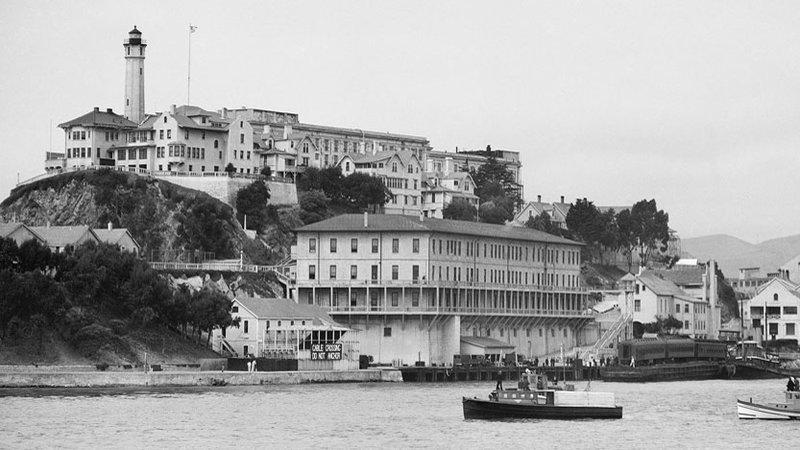 Recettes d'Alcatraz : photo noir et blanc d'Alcatraz avec le bâtiment 64 au premier plan